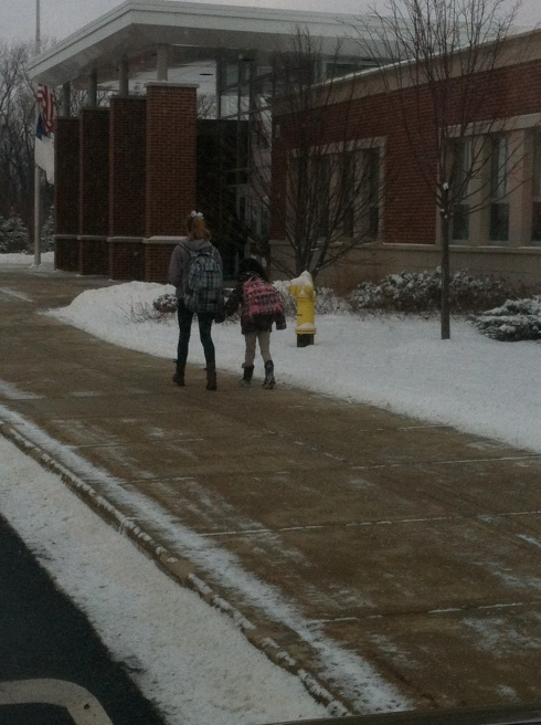 Gigi helping Lainee into school this morning, carrying Lainee's cup of steamed milk for her.