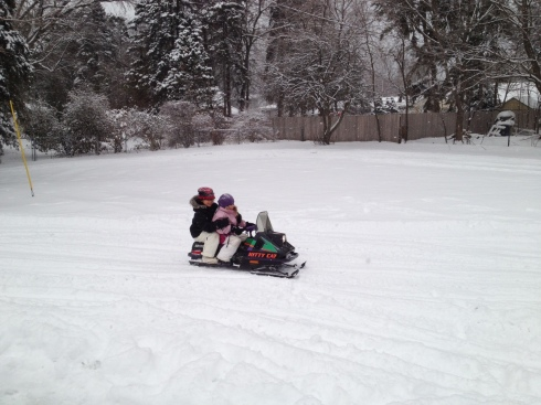 Lainee driving mimi on the mini snowmobile!